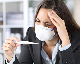 Photo of business woman holding a thermometre and wearing a mask